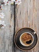 istock Cup of fresh made coffee and spring branches of white flowers of cherry on a vintage wooden background, top view flat lay. 1219434195