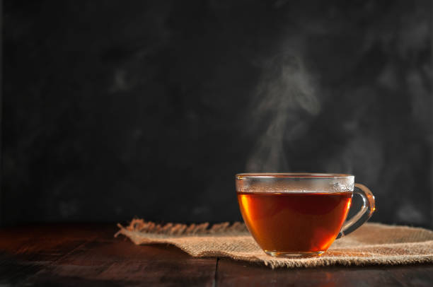 a cup of freshly brewed black tea,escaping steam,warm soft light, darker background. - tea hot drink stock photos and pictures