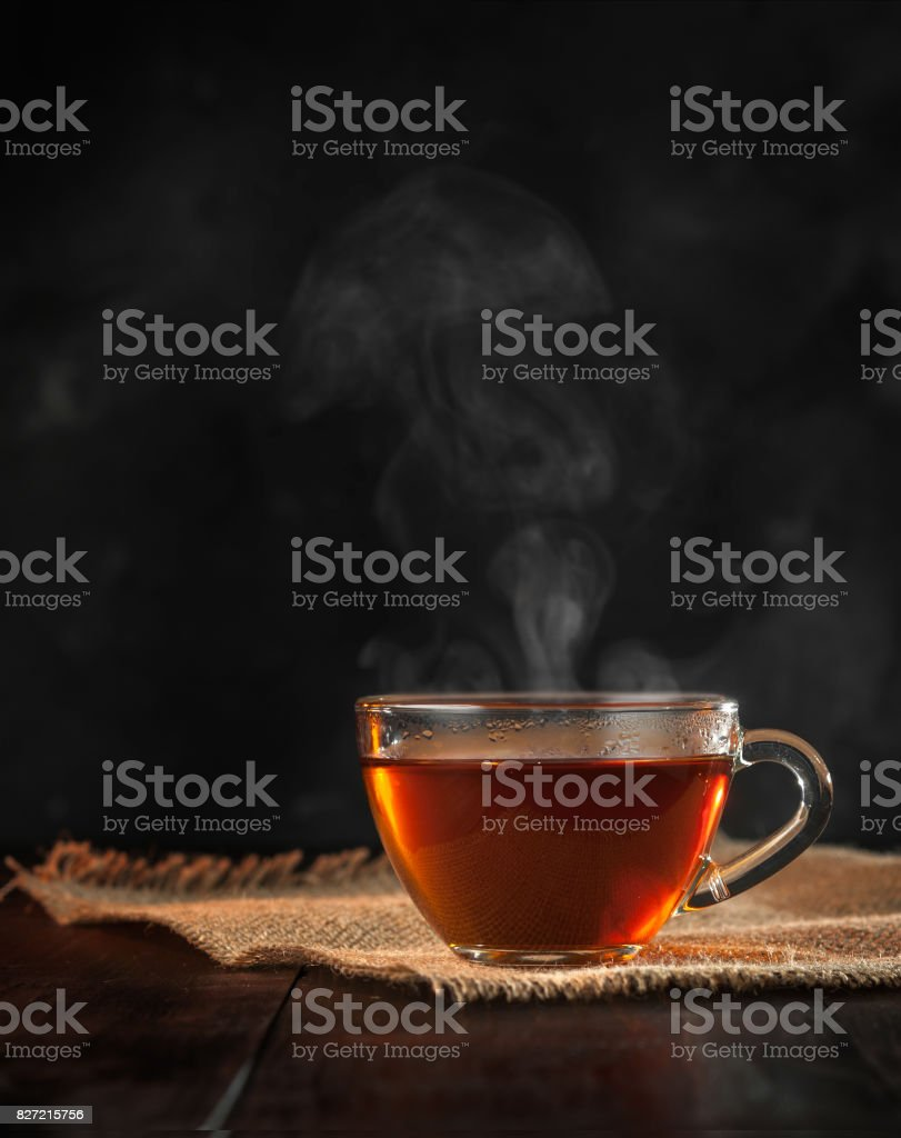 A Cup of freshly brewed black tea,escaping steam,warm soft light, darker background. stock photo