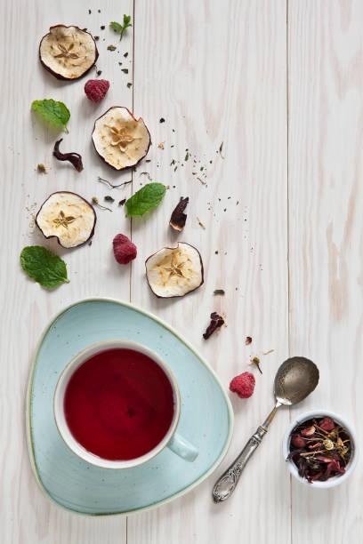 Uma xícara de chá de frutas e seus ingredientes. Vista superior sobre um fundo branco de madeira - foto de acervo