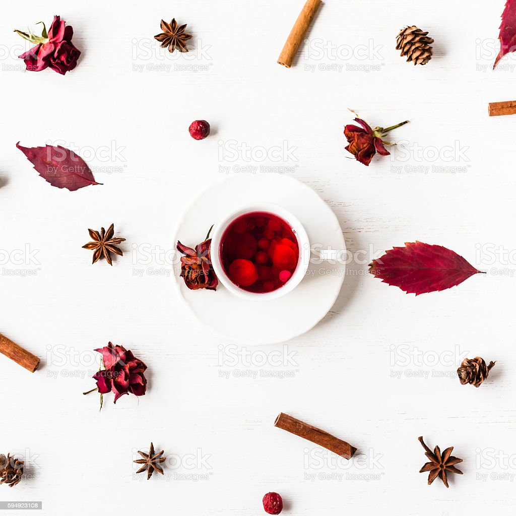 cup of fruit tea with autumn leaves, dried rose flowers stock photo