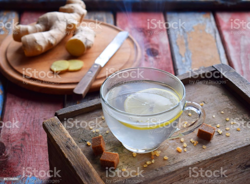 Cup of ginger tea with lemon and brown sugar on wooden backgraund. Hot drink for cough remedy. Traditional medicine and natural health care concept. Copy space for text stock photo