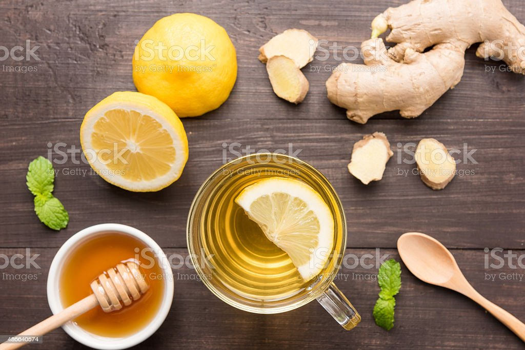 Cup of ginger tea with lemon and honey on table. stock photo