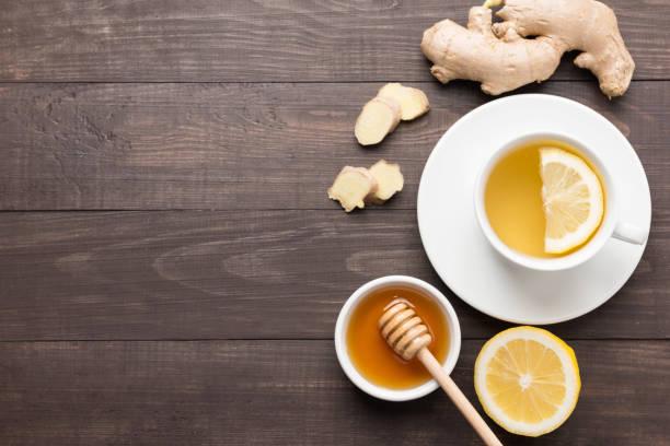 tasse tee mit zitrone und ingwer-honig auf tisch. - heiße zitrone stock-fotos und bilder
