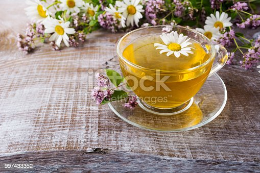 Glass cup of green camomile tea and wild herbs on the rustic wooden background. Herbal organic tea as wellness and relax concept