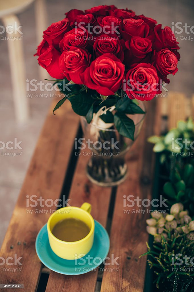Cup of green tea and a bouquet of roses stock photo