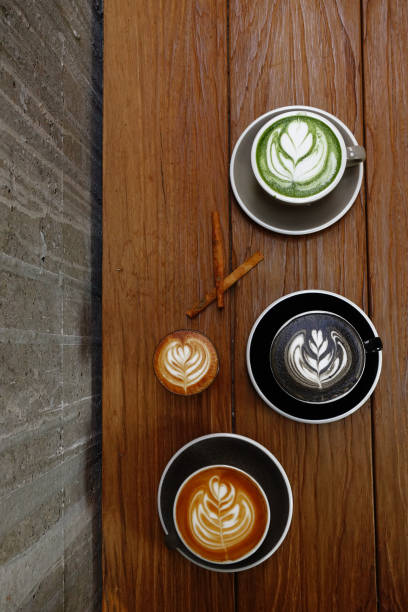 eine tasse grünen tee matcha latte und latte art kaffee - grüner tee koffein stock-fotos und bilder