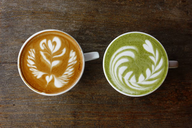 A cup of green tea matcha latte and cup of latte art coffee stock photo