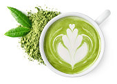 Cup of green tea matcha latte foam art with powder and fresh leaves isolated on white background, top view