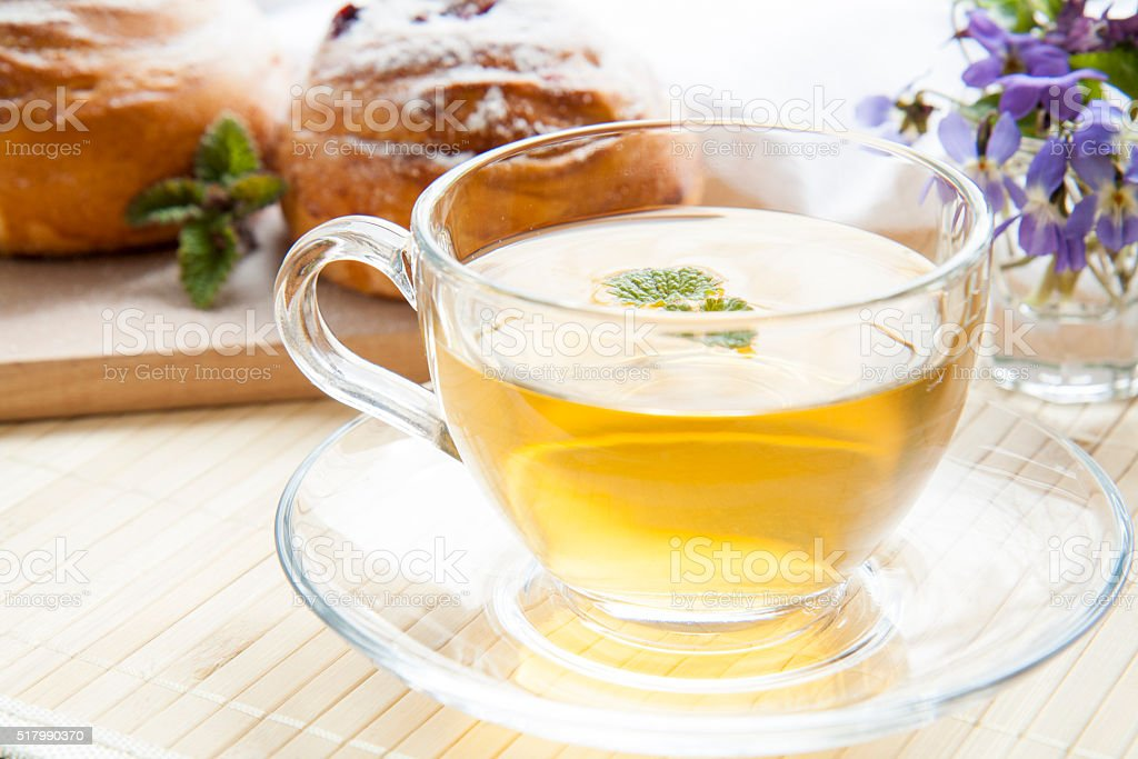 Cup of green tea with lemon balm and tasty rolls royalty-free stock photo