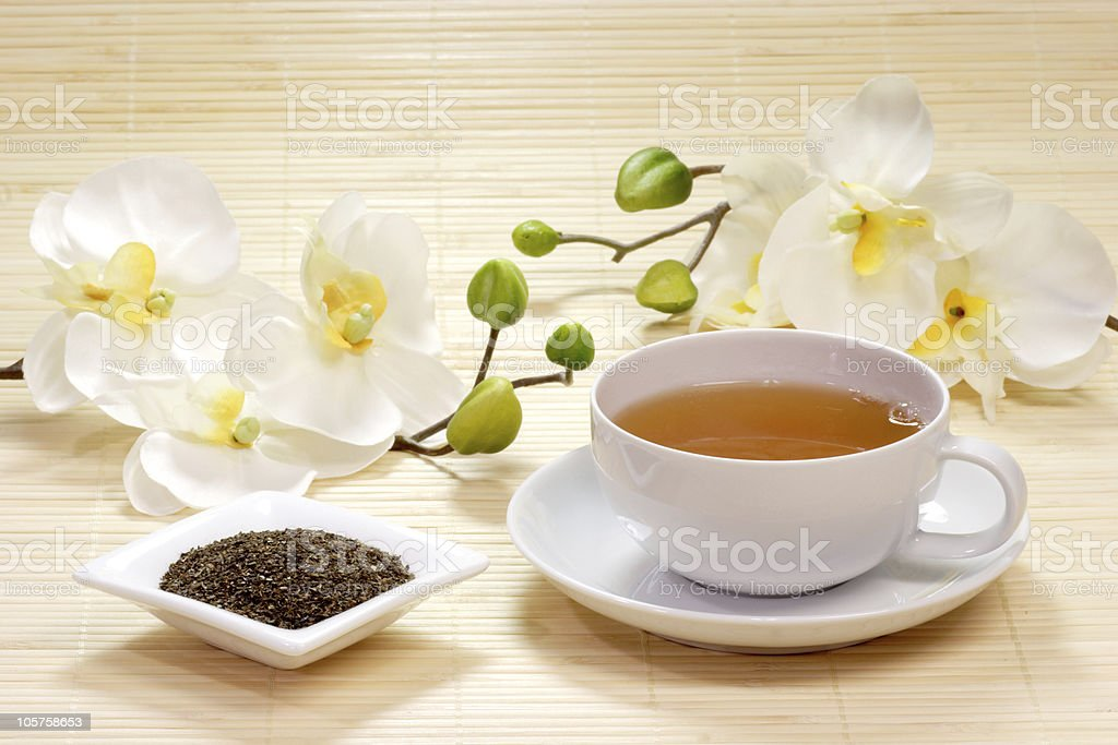 Cup of green tea with white flowers and tea leaves royalty-free stock photo