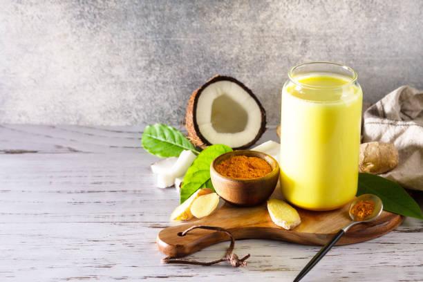 건강한 아유르베다 음료 골든 코코넛 밀크 심황 아이스 라떼와 커큐마 파우더를 주방 테이블에 컵. 공간을 복사합니다. 스톡 사진
