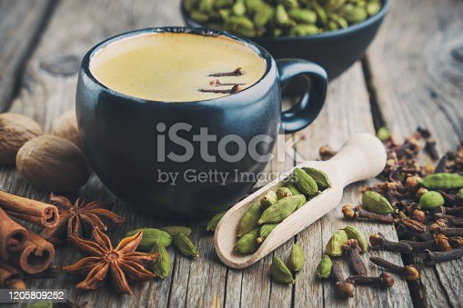 Cup of healthy ayurvedic masala tea or coffee with aromatic spices. Cinnamon sticks, cardamom, allspices and anise on wooden table.