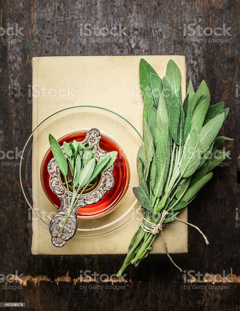 Cup of herbal sage tea with old strainer, books stock photo