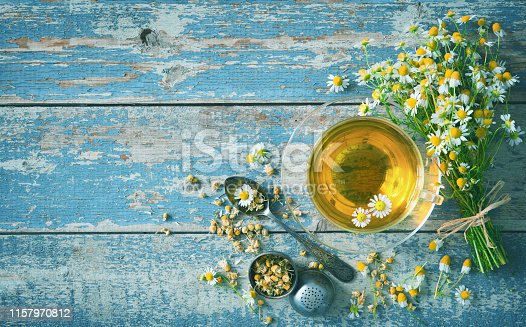 Cup of herbal tea with chamomile flowers on aged blue wood plank. Healthy drink