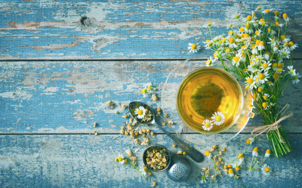 copo do chá erval com as flores da camomila na prancha de madeira azul envelhecida - chá bebida quente - fotografias e filmes do acervo