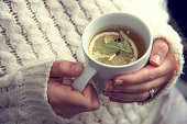 Hand Holding A Cup Of Herbal Tea With Lemon Slice And Clove.