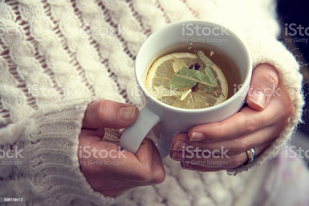Cup Of Herbal Tea With Lemon Slice And Cloves stock photo