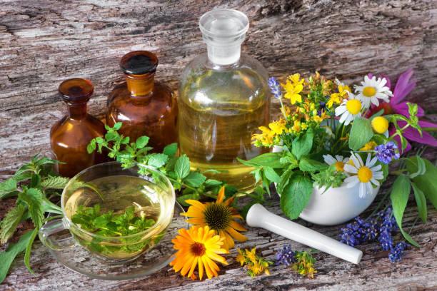 cup of herbal tea with medicinal bottles and healing herbs in mortar - menta erba aromatica foto e immagini stock