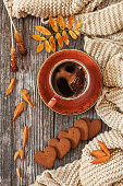 Cup of hot black coffee and heart-shaped gingerbread with autumnal leaves and warm scarf. Autumn background, top view, close-up on wooden vintage table.