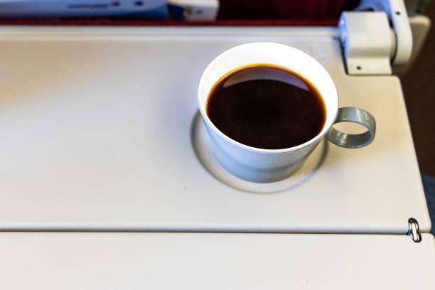 Tasse heißen schwarzen Kaffee am Tisch in Flugzeug-Kabine – Foto