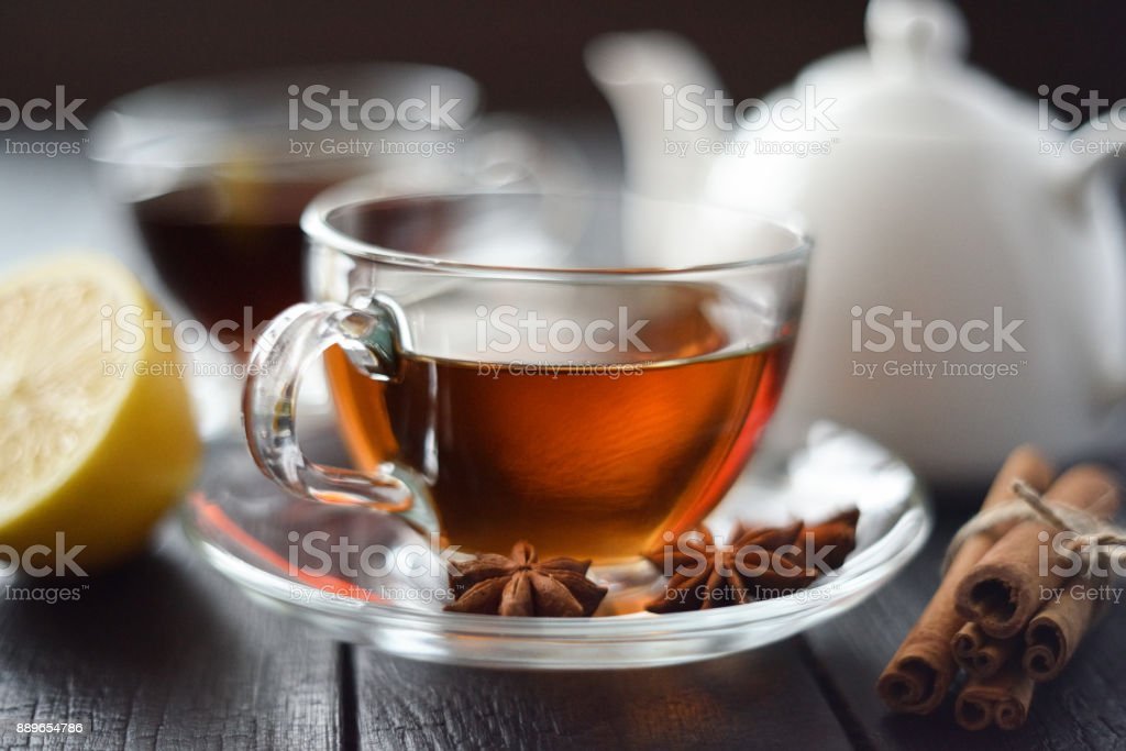 Cup of hot black tea with lemon and spices in glass cup on black background selective focus stock photo