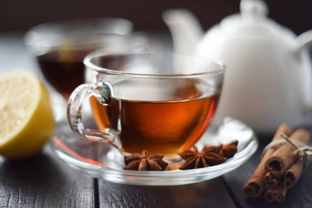 Tasse de thé noir chaud au citron et épices en coupe en verre sur la mise au point sélective de fond noir - Photo