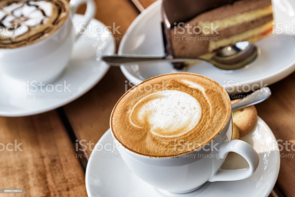 Cup of hot Cappuccino coffee on wooden table at cafe foto stock royalty-free