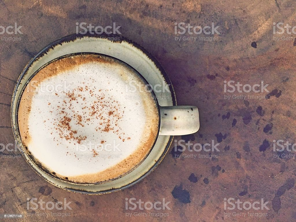 Cup of hot cappuccino over foam milk on the table royalty-free stock photo