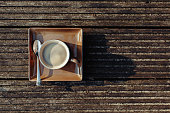 Cup of hot cappucino on the wooden table. Early morning breakfast