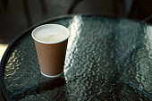 Cup of hot cappucino on a glass table. Early morning breakfast