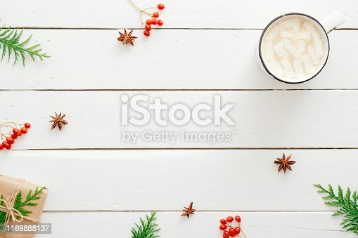 Cup of hot chocolate with marshmallow, fir tree branches, gift, red berry, Christmas decorations on wooden white background. Flat lay, top view, copy space. Winter holidays, Christmas concept.