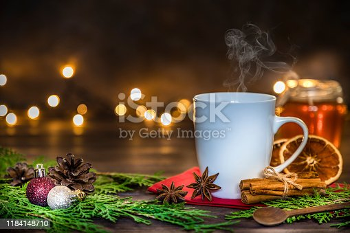 Front view of a hot white cup surrounded by star anise, cinnamon sticks, dried orange slices and some Christmas decoration like pine twigs, Christmas balls and pine cones. At the background are some defocused christmas lights and can be used as a useful copy space. Low key DSLR photo taken with Canon EOS 6D Mark II and Canon EF 24-105 mm f/4L