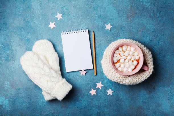 Cup of hot cocoa decorated knitted scarf with marshmallow, mittens and clean notebook top view. Flat lay style. Winter mockup. stock photo