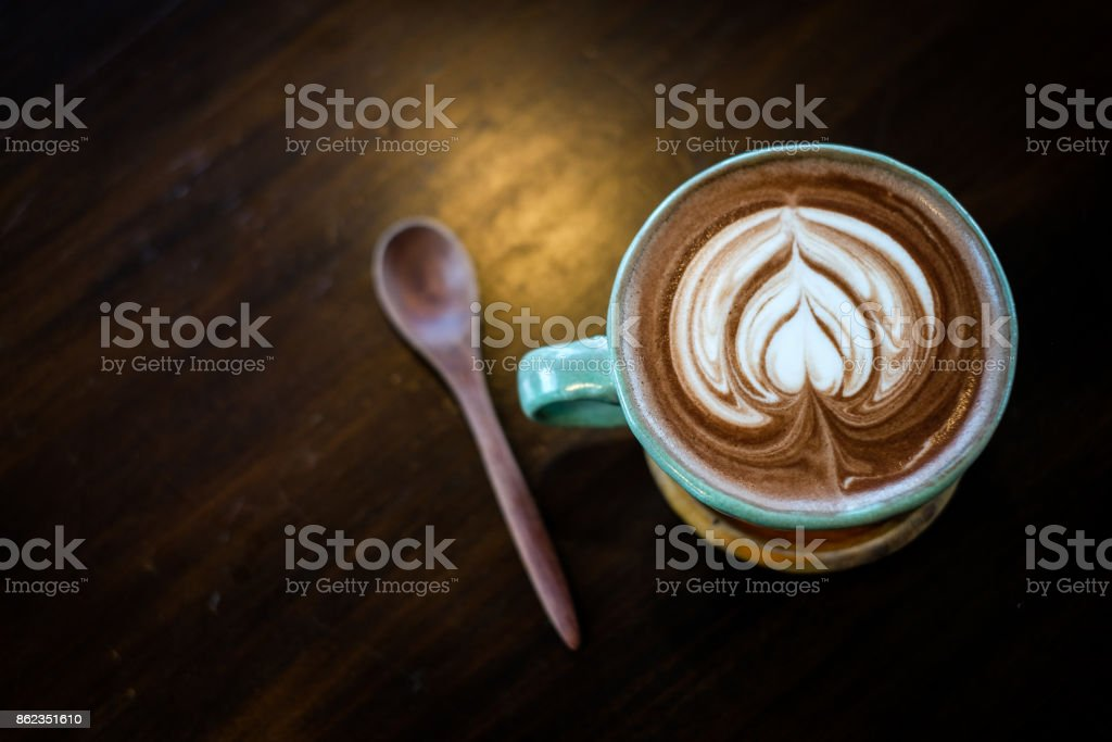 A cup of hot cocoa decorated with heart milk forth on the surface placed on a wooden tray and wooden spoon, for beverage/drink background or texture healthy diet concept. stock photo