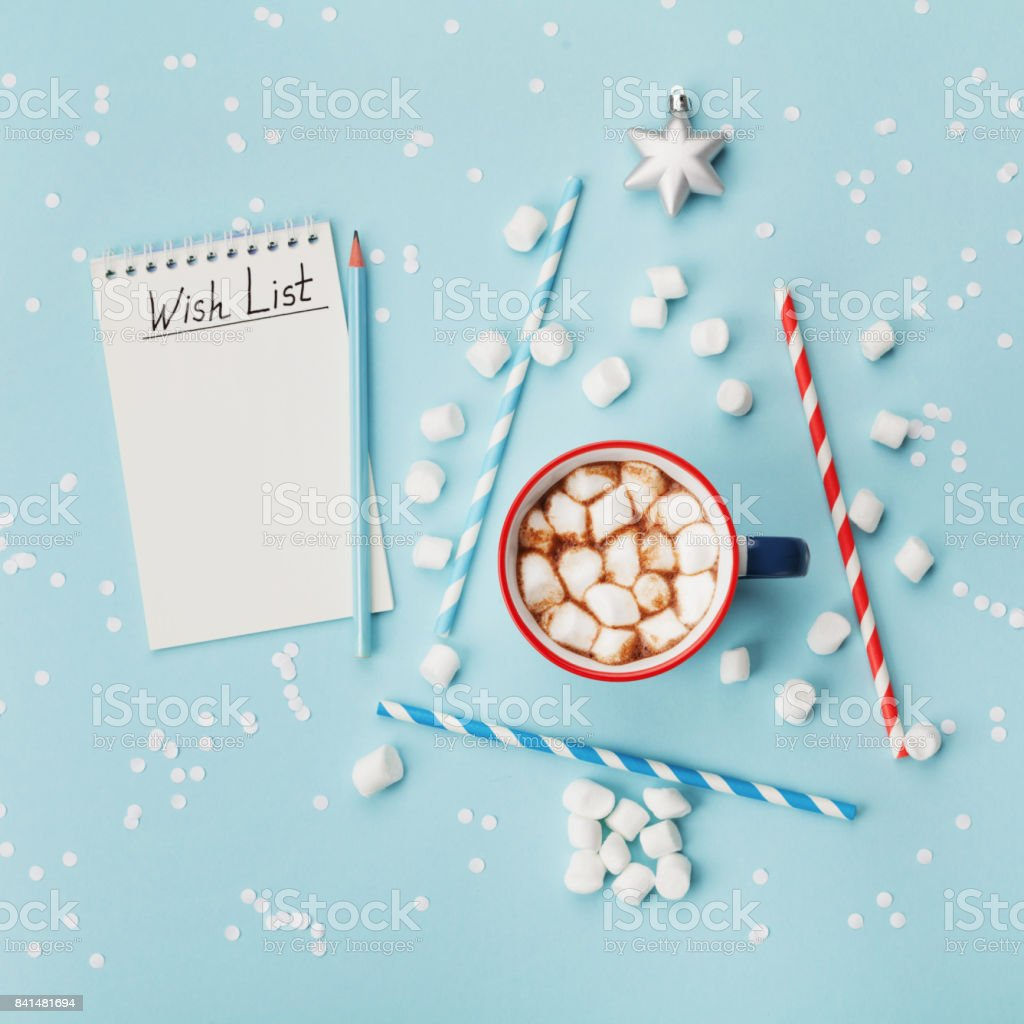 Cup of hot cocoa or chocolate, stylish fir tree and wish list on turquoise confetti background top view. Christmas or new year concept. stock photo