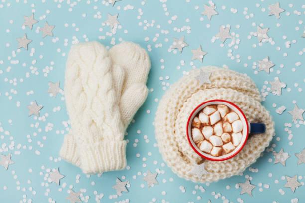 tasse heißen kakao oder schokolade mit marshmallow und gestrickte handschuhe blau winter hintergrund draufsicht. flach zu legen. - schal mit sternen stock-fotos und bilder