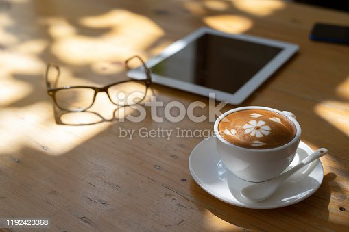 istock Cup of hot coffee and digital tablet on wooden table at coffee shop. Coffee cup on wooden table background. 1192423368
