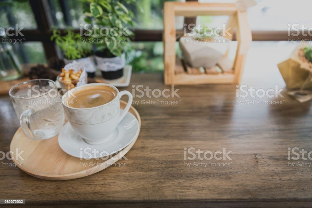 Cup of hot coffee in circle wooden tray on wooden counter in coffeeshop ロイヤリティフリーストックフォト