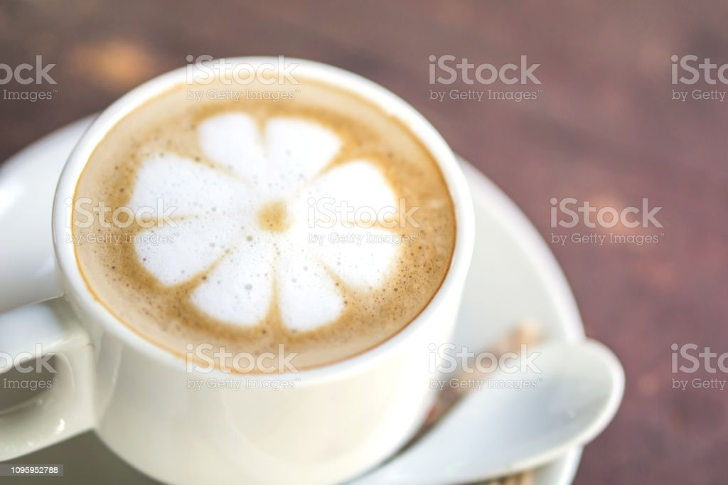 closeup cup of hot coffee latte flower art on wooden table at cafe...