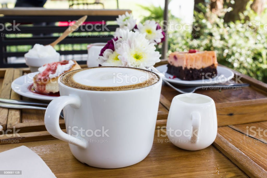 Cup of hot coffee on wooden table  with background of cake and flower stock photo