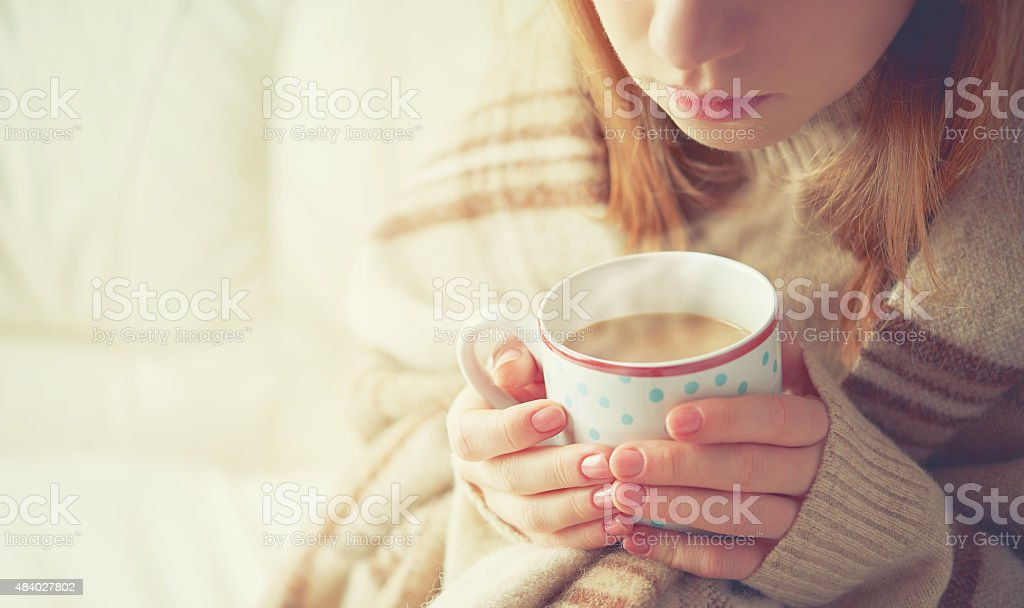 cup of hot coffee warming in the hands of girl stock photo