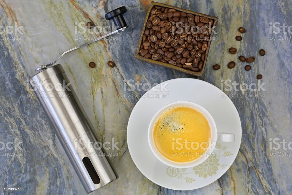 Cup of hot coffee with hand coffee grinder to grind beans. Top view of mini grinding made of steel with handle to make freshly ground coffee stock photo