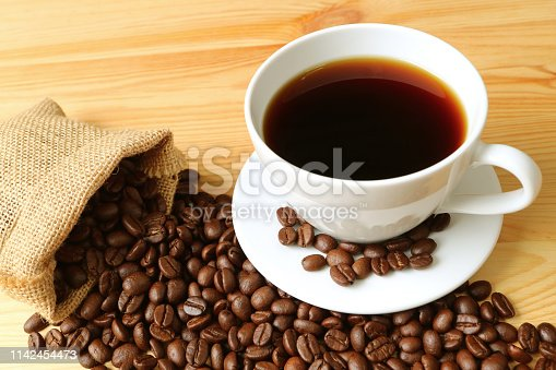 Cup of hot coffee with roasted coffee beans scattered from hemp sack on wooden table