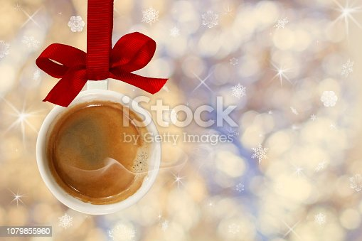 istock Cup of hot coffee with smoke made from Christmas ball, bauble hangs on red ribbon on background of defocused silver lights 1079855960