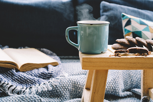 Cup of hot drink on wooden table. Living room interior with blue sofa on background.