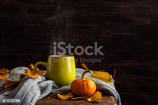A cup of hot drink on a dark background. Autumn.