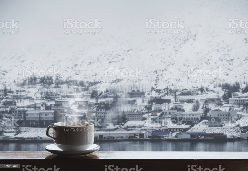 Cup of hot drink with steam on wood table, winter village in winter view stock photo
