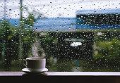 雨の日の木製テーブルでホットド リンクのカップ