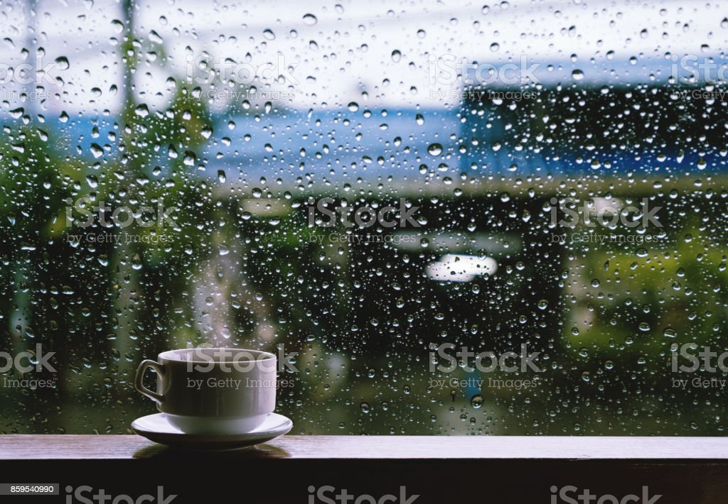 Cup of Hot Drinks on wooden table in rainy day stock photo
